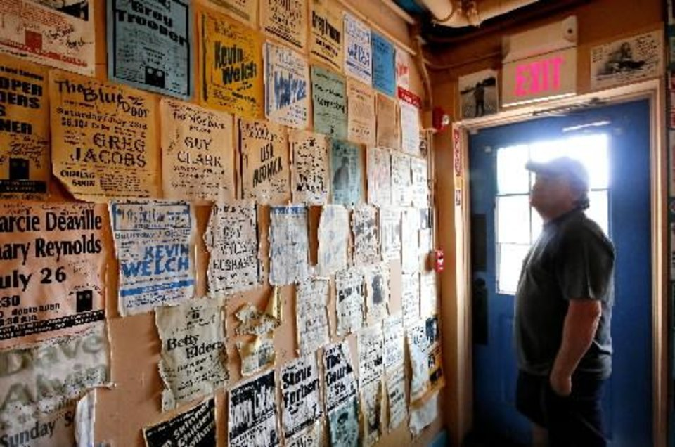 Photo -  Blue Door owner Greg Johnson looks at the posters and pictures from the many shows he has hosted at his beloved listening room the Blue Door, 2805 N McKinley. The venue, which is also Johnson's home, is celebrating its 20th anniversary. Photo by Jim Beckel, The Oklahoman