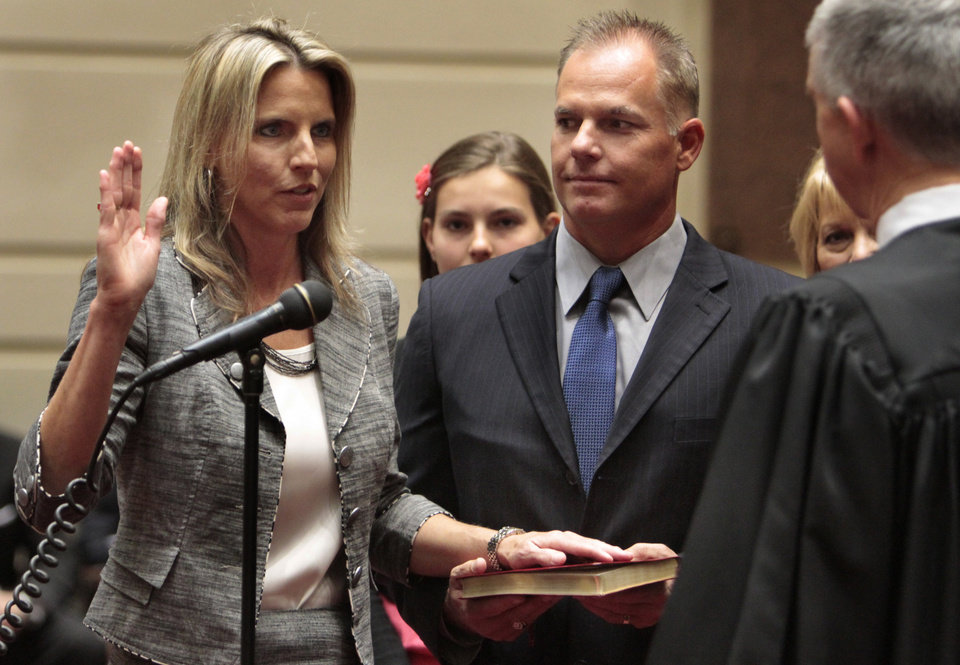 "Ann ""A.J."" Griffin, Guthrie, takes the oath of office as state senator on Wednesday, April 11, 2012, in Oklahoma City, Okla. Her husband Trey Griffin holds the Bible as Justice Steven Taylor presides.  Photo by Steve Sisney, The Oklahoman"