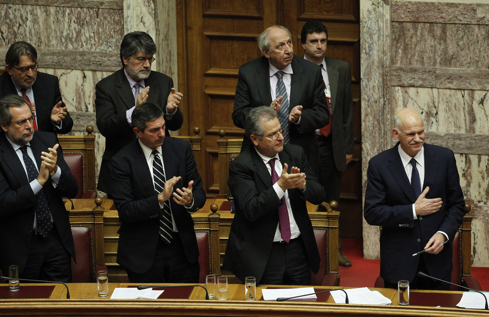 Photo - Lawmakers applaud Greek Prime Minister George Papandreou, right, after his speech during a parliament session in Athens, Thursday, Nov. 3, 2011. Papandreou abandoned his explosive plan to put a European rescue deal to popular vote Thursday, keeping his government alive _ but passionate squabbling in Athens left the country's solvency in doubt and the eurozone in turmoil. Greek Prime Minister reversed course after a rebellion within his own Socialist party over the referendum, but ignored repeated calls to resign and call elections. (AP Photo/Petros Giannakouris) ORG XMIT: XPG116
