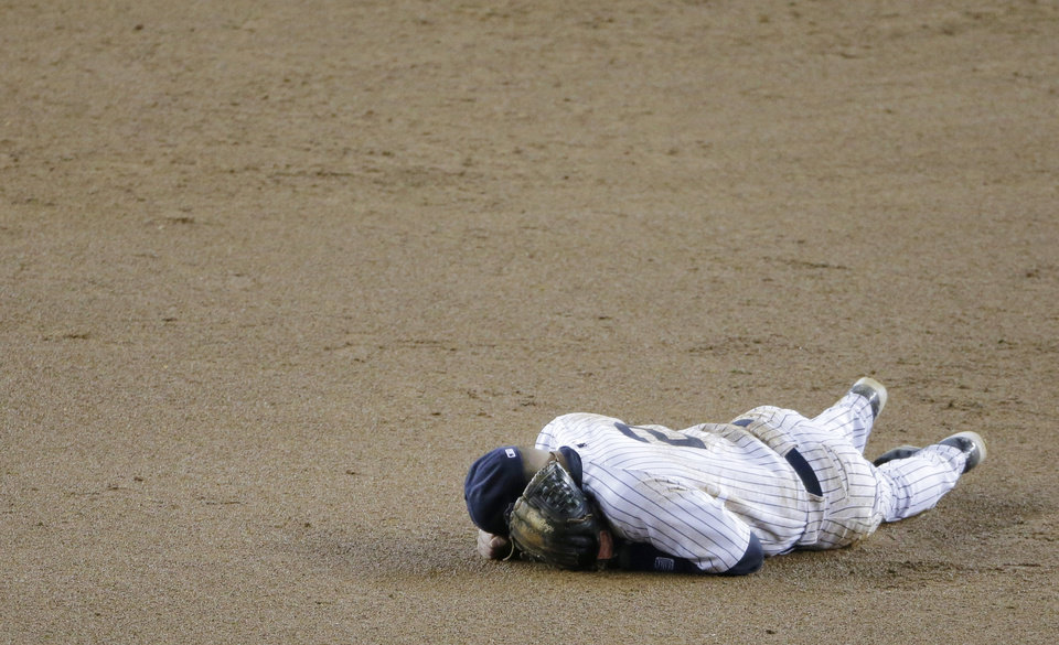 Photo -   New York Yankees shortstop Derek Jeter lays on the infield after injuring himself in the 12th inning of Game 1 of the American League championship series against the Detroit Tigers Sunday, Oct. 14, 2012, in New York. (AP Photo/Charlie Riedel)