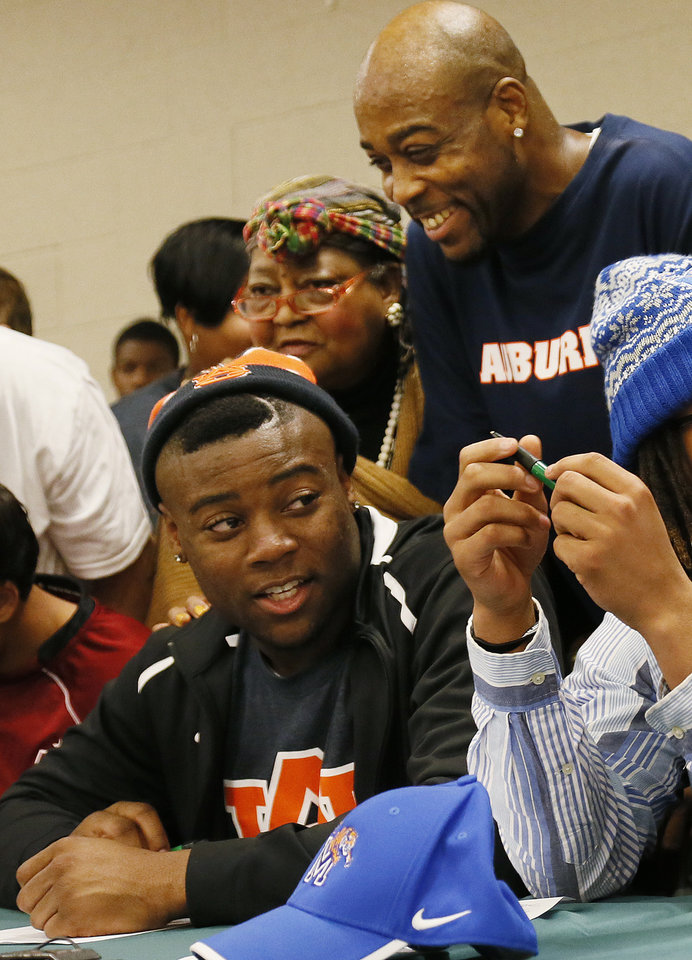 Photo - Corie Harding, upper right, watches his son Khari Harding sign to play football at Auburn during the signing day ceremony at Edmond Santa Fe High School in Edmond, Okla., Wednesday, Feb. 6, 2013. Next to Corie Harding is Khari Harding's grandmother, Mary Harding. Photo by Nate Billings, The Oklahoman