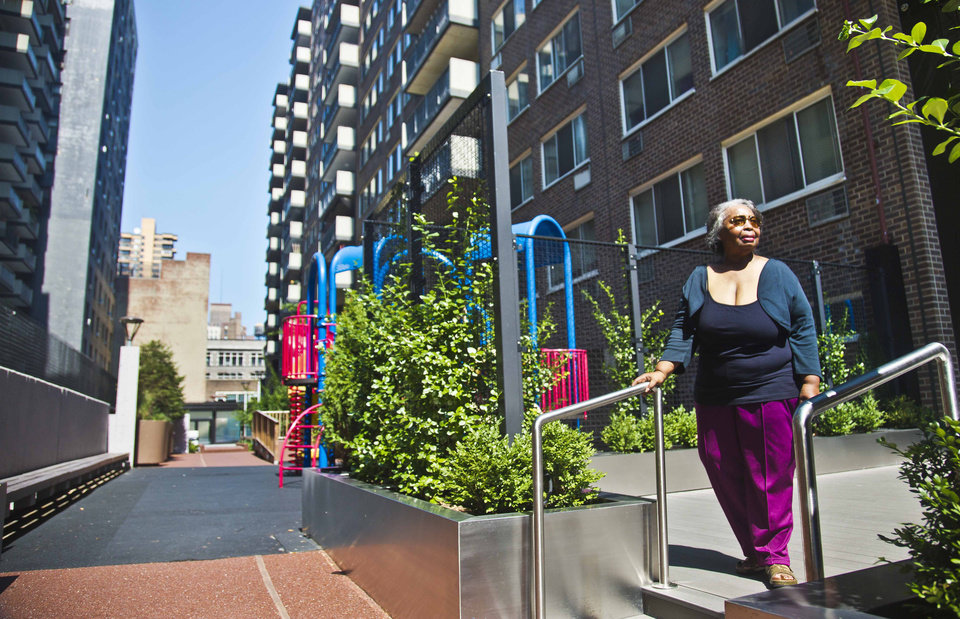 Photo - In this Aug. 5, 2014 photo, Jean Green Dorsey walks outside the building on New York City's Upper West Side where she has lived since 1972. Dorsey has a rent stabilized unit in a building that also houses market rate residents. As a rent stabilized tenant, Dorsey is not allowed to use the new gym that market rate residents use for free, even if she paid for the privilege. (AP Photo/Bebeto Matthews)