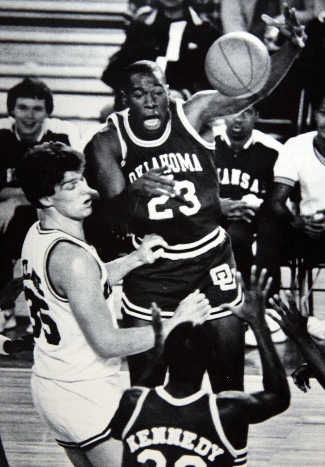 Former OU basketball player Wayman Tisdale. Oklahoma's Wayman Tisdale leaps high as he gets a pass to teammate Darryl Kennedy as Arkansas' Joe Kleine defends during the Sooners' 84-78 loss to the Razorbacks in the Great Alaska Shootout on Saturday night. Photo taken unknown, Photo published 11/27/1983 in The Daily Oklahoman. ORG XMIT: KOD