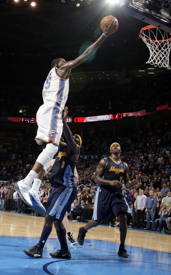 Photo - Oklahoma City's Kevin Durant (35) shoots a lay up over Denver's Ty Lawson (3) during the NBA basketball game between the Oklahoma City Thunder and the Denver Nuggets at the Chesapeake Energy Arena, Sunday, Feb. 19, 2012. Photo by Sarah Phipps, The Oklahoman