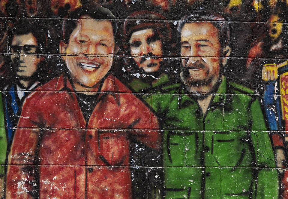 Photo - FILE - In this Feb. 22, 2012 file photo, a mural featuring Venezuela's President Hugo Chavez, left, and Cuba's Fidel Castro, adorns a wall in Caracas, Venezuela. Under Chavez's leadership, Venezuela has sent billions of dollars a year to Cuba through trade and petro-aid, supplying about half of the island's energy needs at greatly subsidized rates. The Venezuelan president regularly calls Fidel Castro his ideological father and has followed much of the Communist legend's governance and foreign relations playbook. (AP Photo/Ariana Cubillos, File)