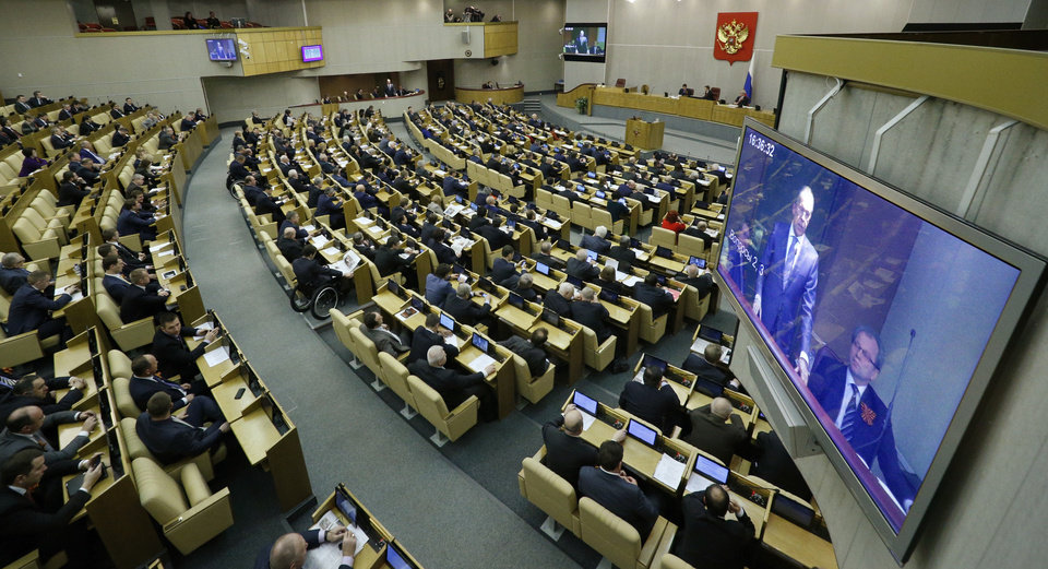 Photo - Members of the State Duma, lower parliament chamber, listen to Russian Foreign Minister Sergey Lavrov, seen on the screen, prior to voting during a plenary session in Moscow, Russia, Thursday, March 20, 2014. The Kremlin-controlled State Duma voted Thursday to allow Crimea to join Russia following a quick discussion in which members of the Kremlin-controlled chamber assailed the Ukrainian authorities. The merger needs to be rubber stamped by the upper house and signed by President Vladimir Putin, mere formalities expected to be completed by the end of the week. (AP Photo/Alexander Zemlianichenko)