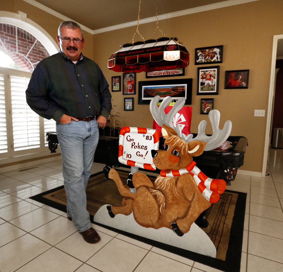 Photo - Randy Chelf  talks about his son, Oklahoma State University quarterback Clint Chelf, and the impact his notoriety has on his hometown on Wednesday, Dec. 18, 2013 in Enid, Okla.  The Chelf house does not lack for OSU decorations.  Photo by Steve Sisney, The Oklahoman