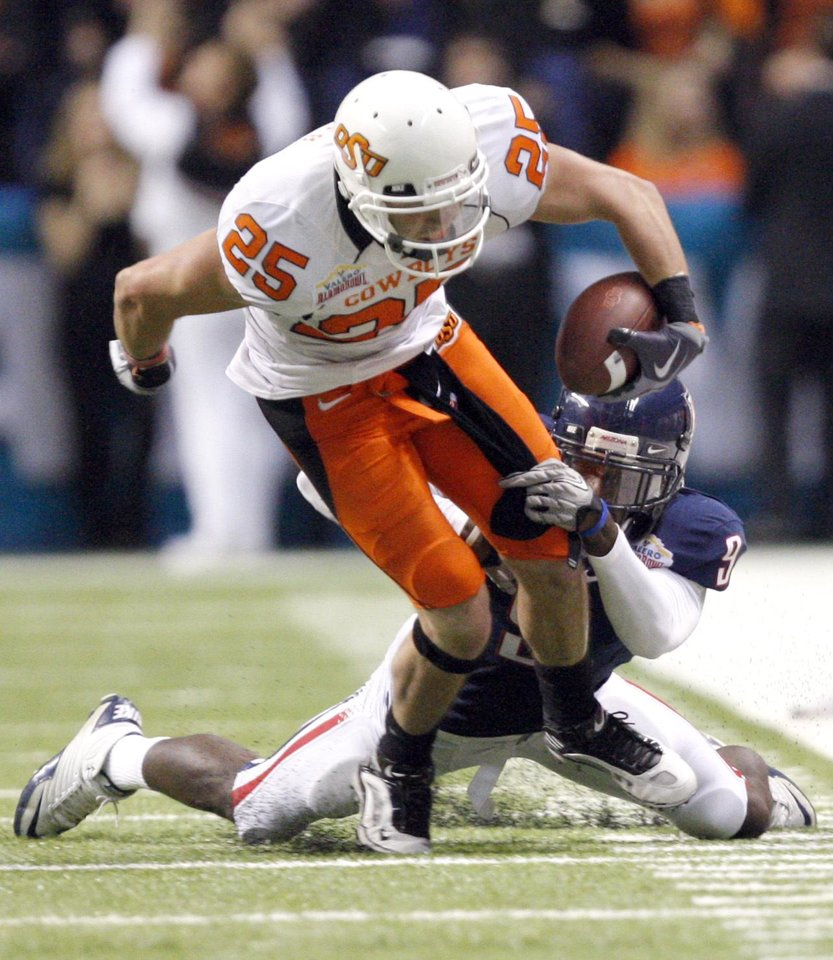 Photo - Oklahoma State's Josh Cooper (25) is brought down by Arizona's Joseph Perkins (9) during the Valero Alamo Bowl college football game between the Oklahoma State University Cowboys (OSU) and the University of Arizona Wildcats at the Alamodome in San Antonio, Texas, Wednesday, December 29, 2010. OSU won, 36-10. Photo by Sarah Phipps, The Oklahoman