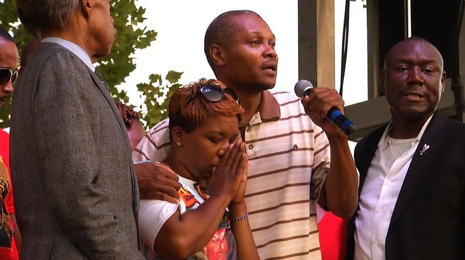 Photo - Lesley McSpadden, Michael Brown's mother, second from left, stands next to her cousin, Eric Davis, as he addresses  the crowd at Peace Fest, Sunday, Aug. 24, 2014, in St. Louis. Hundreds of people gathered in St. Louis' largest city park Sunday at a festival that promoted peace over violence. (AP Photo/Alex Sanz)