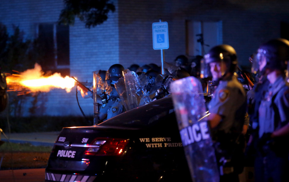 Photo - An Oklahoma City Police officer fires a non-lethal weapon in front of the Oklahoma City Police Department in Oklahoma City, Sunday, May 31, 2020. The protest was in response to the death of George Floyd. [Sarah Phipps/The Oklahoman]