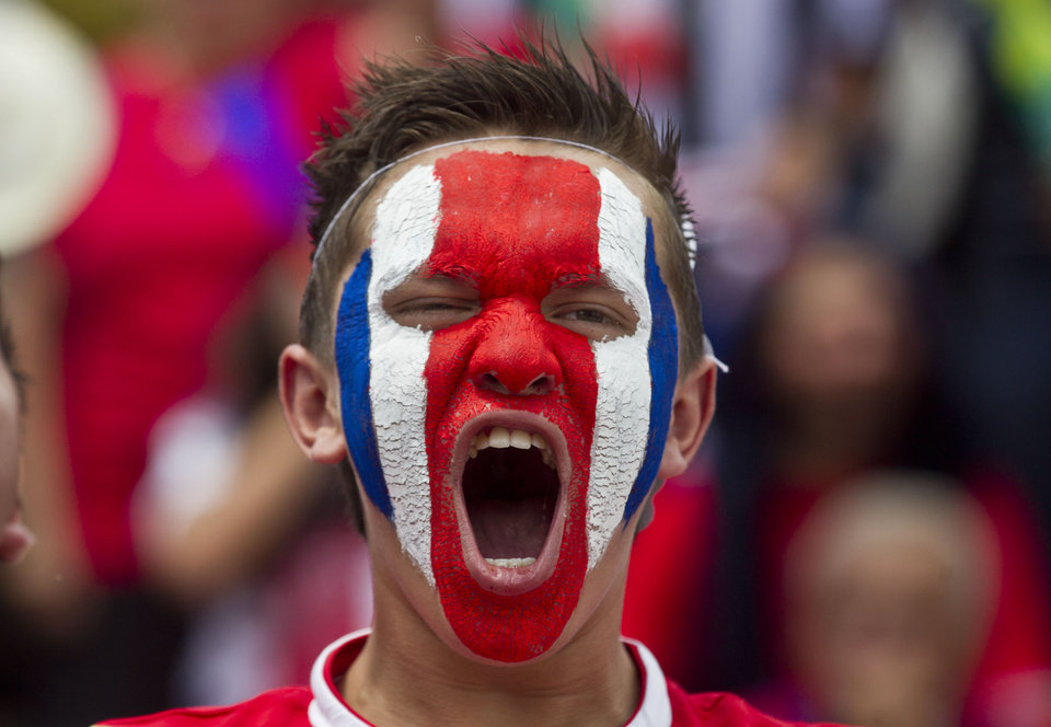 Photo - A Costa Rican soccer fans with his face painted in the country's national colors gets warmed up as he prepares to watch a round of 16 World Cup match against Greece, in San Jose, Costa Rica, Sunday, June 29, 2014. (AP Photo/Esteban Felix)