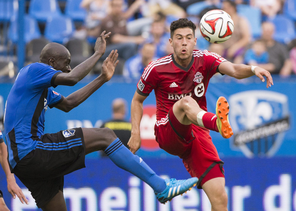 Photo - Montreal Impact's Hassoun Camara, left, moves in on Toronto FC's Jonathan Osorio during the second half of a soccer match in Montreal, Saturday, Aug. 2, 2014. (AP Photo/The Canadian Press, Graham Hughes)