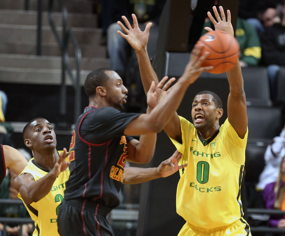 Photo - Southern California's Byron Wesley, center, passes the ball under pressure from Oregon's Damyean Dotson, left, and Mike Moser, right, during the first half of an NCAA college basketball game in Eugene, Ore. on Saturday, Feb. 1, 2014. (AP Photo/Chris Pietsch)