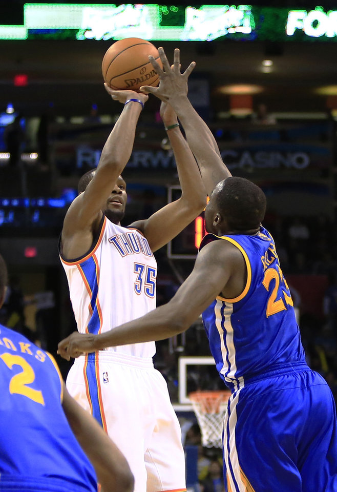 Photo - Oklahoma City Thunder small forward Kevin Durant (35) shoots as Golden State Warriors small forward Draymond Green (23) defends during the fourth quarter of an NBA basketball game Friday, Jan. 17, 2014, in Oklahoma City. Oklahoma City won 127-121. AP Photo/Alonzo Adams)