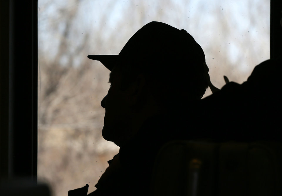 Photo - A passenger is silhouetted as he looks out the window on a demonstration ride of the Eastern Flyer passenger train from Sapulpa to the Oklahoma City metro area, Sunday, Feb. 23, 2014. Photo by Nate Billings, The Oklahoman