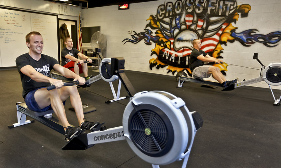 Photo - Joel Brown works on a rowing machine at Crossfit Native in Warr Acres. Photo by CHRIS LANDSBERGER, The Oklahoman