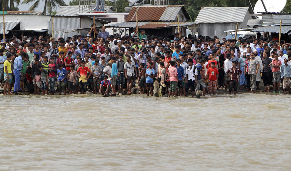 Photo - Bangladeshi people gather on the banks of  the River Padma after a passenger ferry capsized in Munshiganj district, Bangladesh, Monday, Aug. 4, 2014. A passenger ferry carrying hundreds of people capsized Monday in central Bangladesh, and at least 44 people either swam to safety or were rescued but the number of missing passengers is not yet known. (AP Photo/ A.M. Ahad)