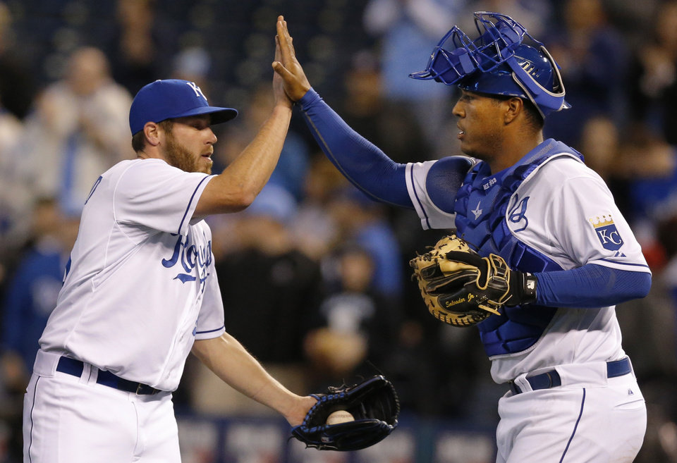 Photo - Kansas City Royals relief pitcher Greg Holland, left, celebrates with catcher Salvador Perez, right, following the MLB American League baseball game against the Tampa Bay Rays at Kauffman Stadium in Kansas City, Mo., Monday, April 7, 2014. The Royals defeated the Rays 4-2. (AP Photo/Orlin Wagner)