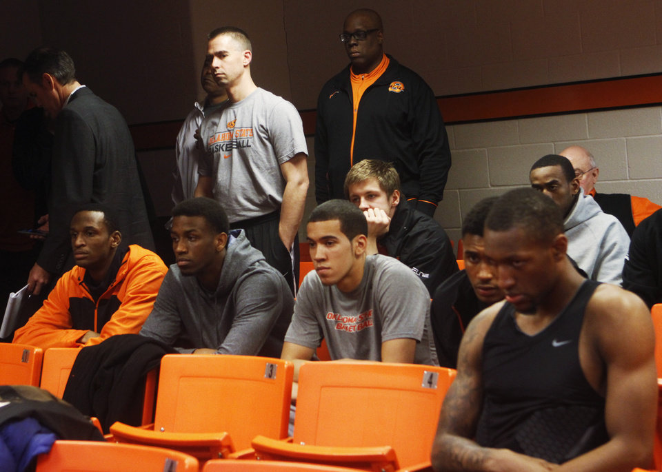 Photo - Members of the Oklahoma State basketball team look on from the back of the room while a press conference is held in Gallagher Iba Arena on Sunday, Feb. 9, 2014. The press conference was held the day after star player Marcus Smart shoved a fan during an altercation in a game Saturday, Feb. 8, 2014. Smart was given a three game suspension by the Big 12 conference and Oklahoma State. Photo by KT King/The Oklahoman