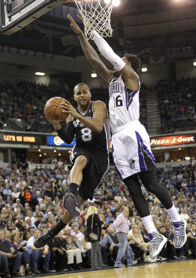 Photo - San Antonio Spurs guard Patty Mills, left,  of Australia, is fouled as he drives to the basket past Sacramento Kings Ben McLemore during the first quarter of an NBA basketball game in Sacramento, Calif., Friday, March 21, 2014.(AP Photo/Rich Pedroncelli)
