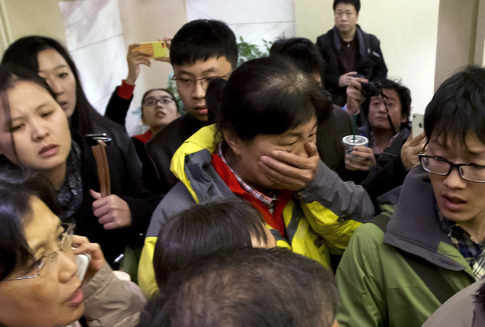 Photo - A woman, center, surrounded by media covers her mouth on her arrival at a hotel which is prepared for relatives or friends of passengers aboard a missing airplane, in Beijing, China Saturday, March 8, 2014. A Malaysia Airlines Boeing 777-200 carrying 239 people lost contact over the South China Sea early Saturday morning on a flight from Kuala Lumpur to Beijing, and international aviation authorities still hadn't located the jetliner several hours later. (AP Photo/Andy Wong)