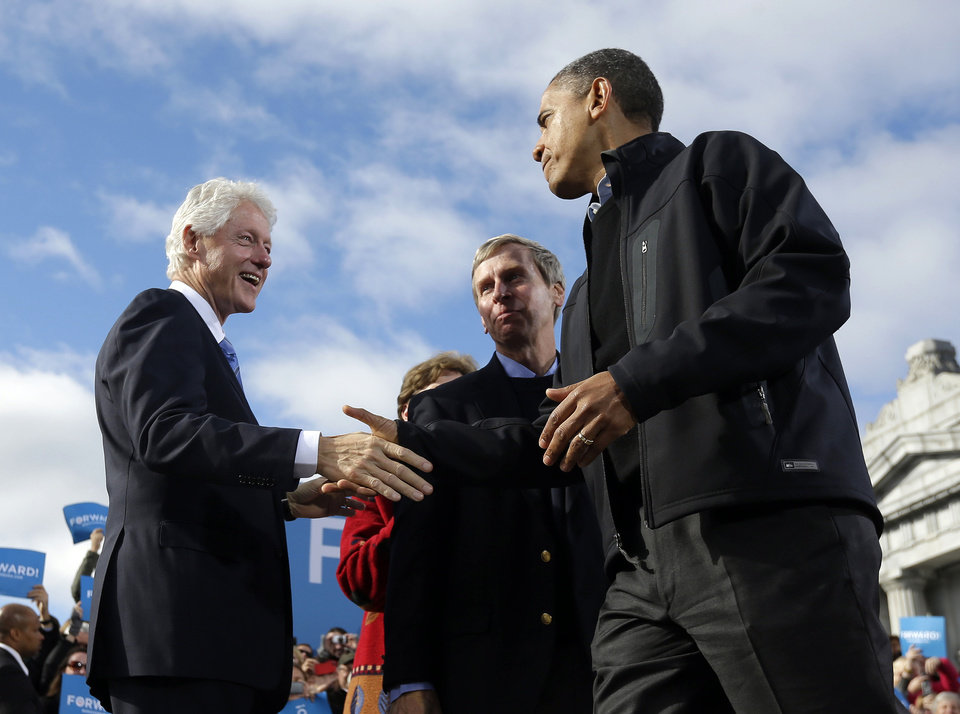 Photo -   President Barack Obama, right, shakes hands with former President Bill Clinton, left, as New Hampshire Gov. John Lynch, center, watches on stage together during a campaign event at Capitol Square, Sunday, Nov. 4, 2012, in Concord, N.H. (AP Photo/Pablo Martinez Monsivais)
