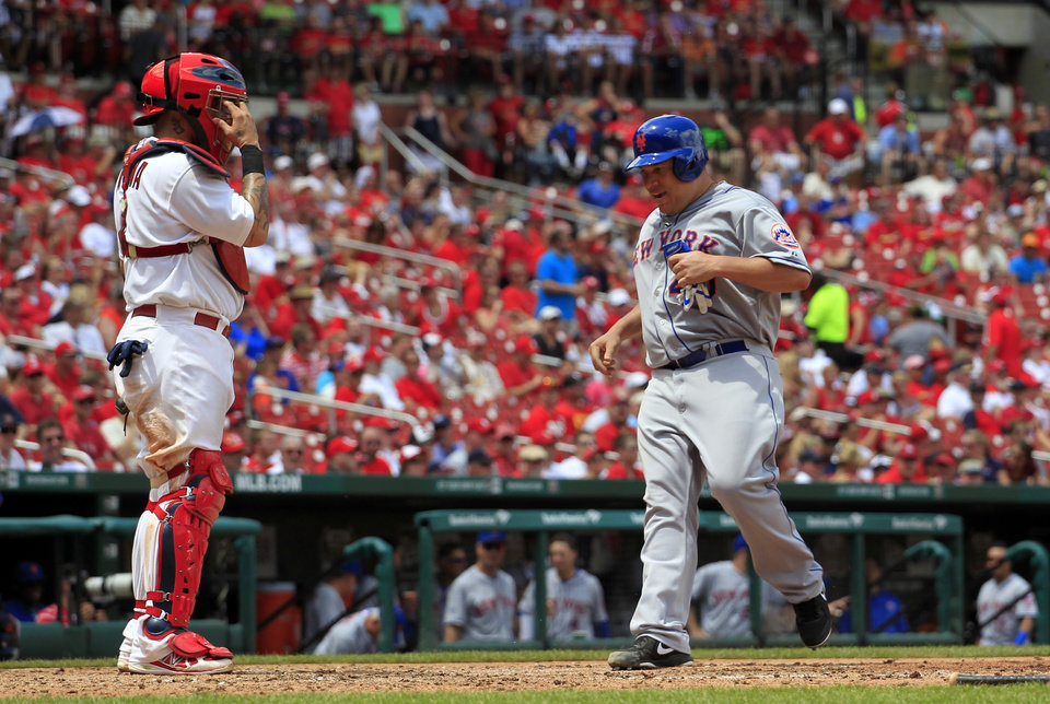 Photo - New York Mets' Bartolo Colon, right, scores on a double by Eric Young Jr. as St. Louis Cardinals catcher Yadier Molina, left, watches during the sixth inning of a baseball game Wednesday, June 18, 2014, in St. Louis. (AP Photo/Jeff Roberson)