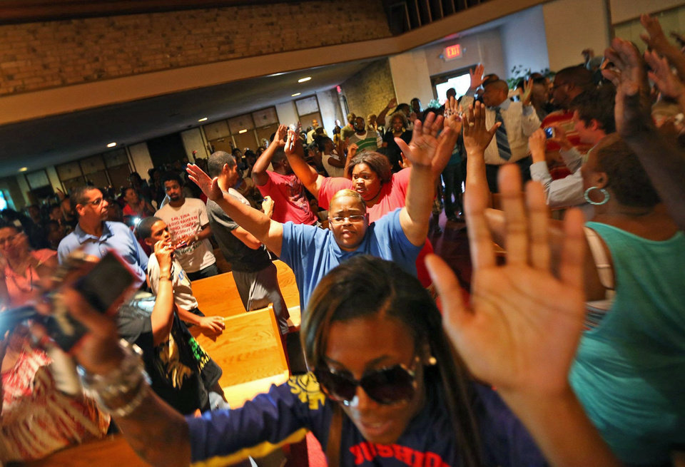 Photo - A group of young protestors left the QuikTrip area, walked to the Greater St. Mark Missionary Baptist Church to join a gathering with Michael Brown's family and Rev. Al Sharpton.  They entered the church chanting,