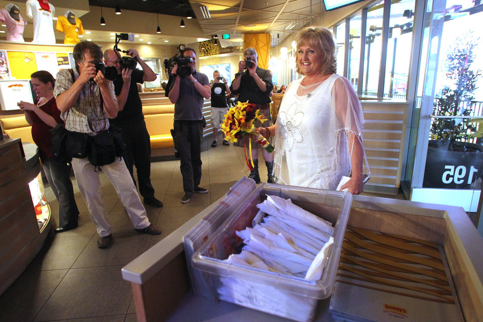 Nancy Levindowski makes her entrance into the Denny's restaurant on Fremont Street in Las Vegas, for her wedding to Steve Keller Wednesday, April 4, 2013. (AP Photo/Las Vegas Sun, Sam Morris)
