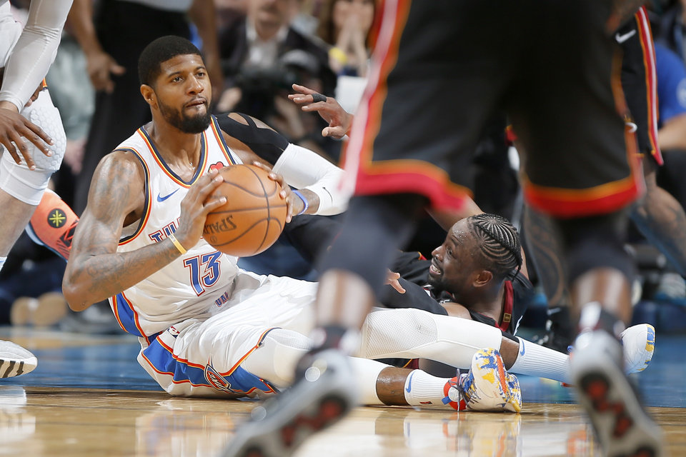 Photo - Oklahoma City's Paul George (13) passes the ball beside Miami's Dwyane Wade (3) during an NBA basketball game between the Oklahoma City Thunder and the Miami Heat at Chesapeake Energy Arena in Oklahoma City, Monday, March 18, 2019. Miami won 116-107. Photo by Bryan Terry, The Oklahoman