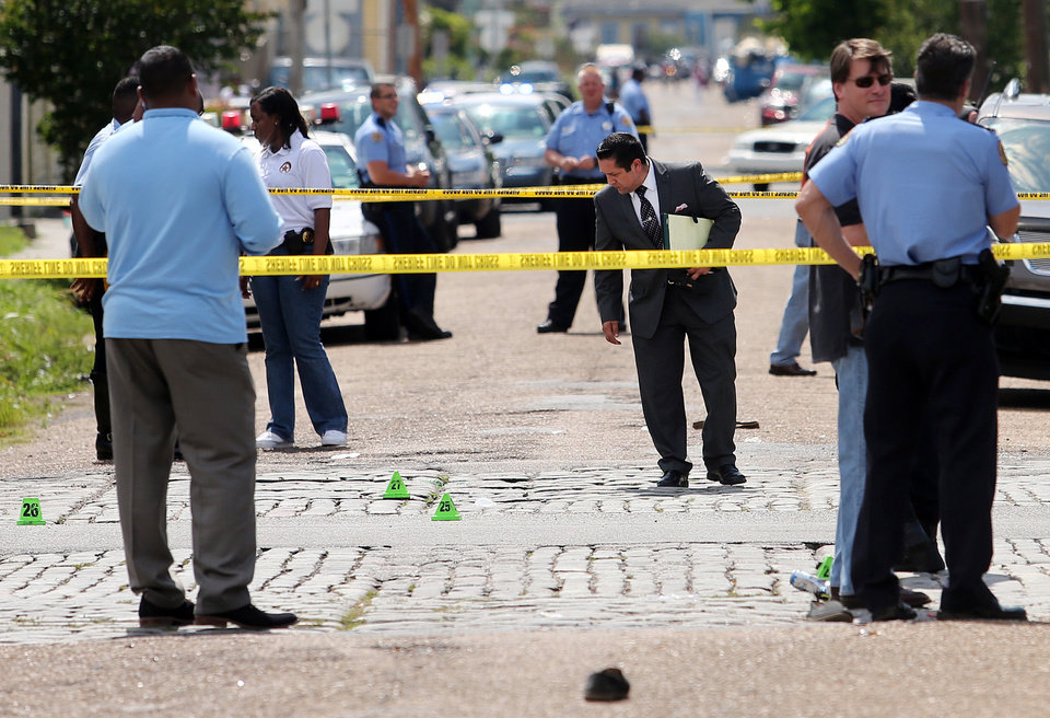 Photo - New Orleans police officers investigate the scene at the intersection of Frenchmen and N. Villere Streets in New Orleans after gunfire at a Mother's Day second-line parade on Sunday, May 12, 2013. Police spokeswoman Remi Braden said in an email that many of the 17 victims were grazed and most of the wounds weren't life-threatening. No deaths were reported. (AP Photo/The Times-Picayune, Michael DeMocker)