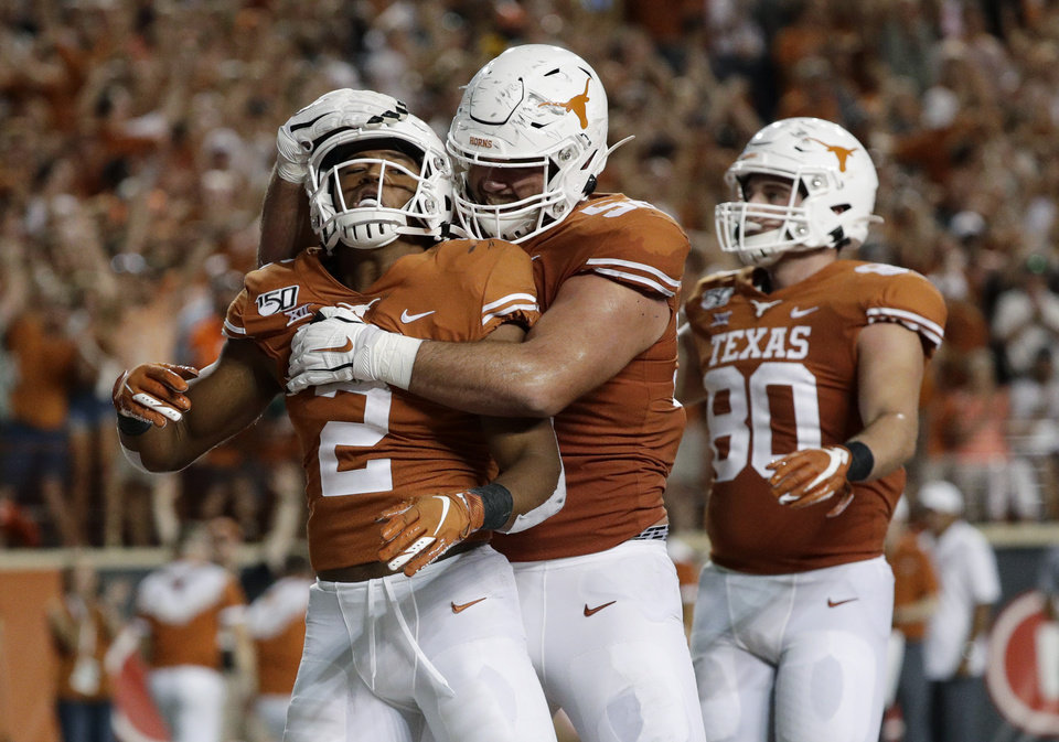 Photo - Texas' Roschon Johnson (2) celebrates his touchdown run with teammates during the second half of an NCAA college football game against Oklahoma State, Saturday, Sept. 21, 2019, in Austin, Texas. (AP Photo/Eric Gay)