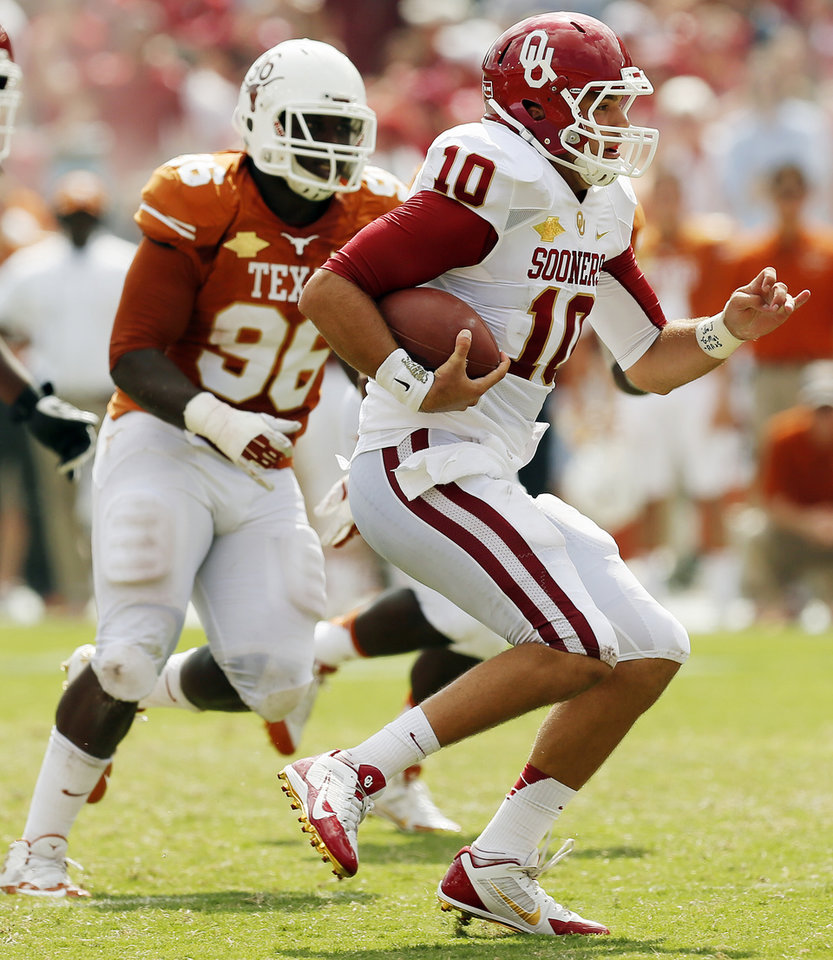 Photo - OU's Blake Bell (10) carries the ball away from UT's Chris Whaley (96) in the third quarter during the Red River Rivalry college football game between the University of Oklahoma Sooners and the University of Texas Longhorns at the Cotton Bowl Stadium in Dallas, Saturday, Oct. 12, 2013. UT won, 36-20. Photo by Nate Billings, The Oklahoman