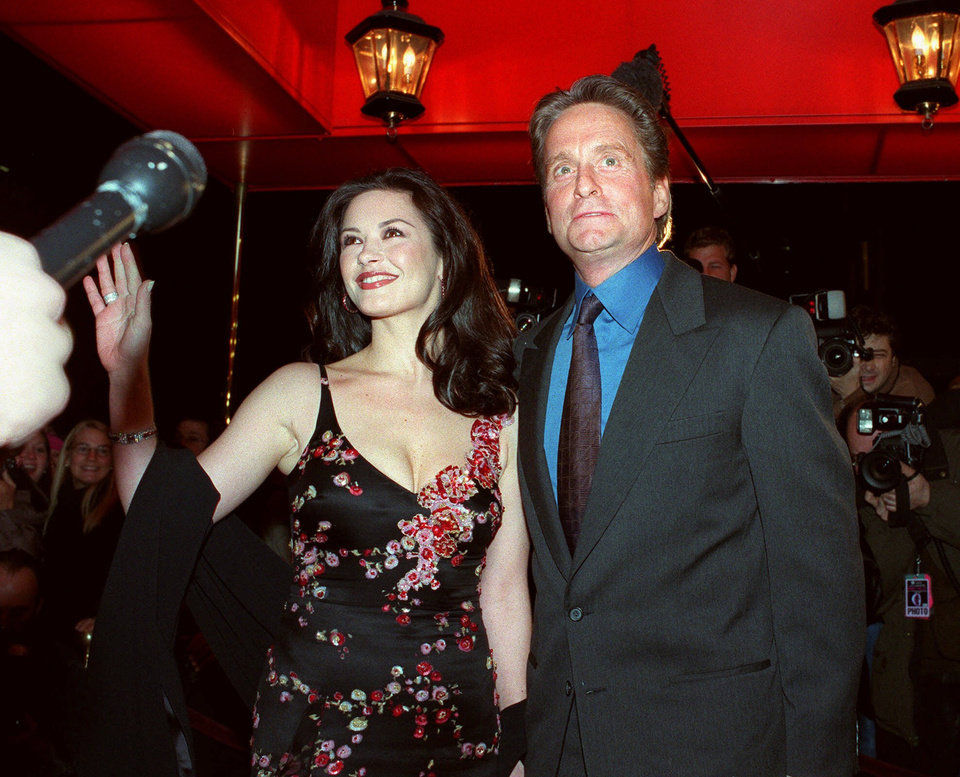 Photo - FILE - In this Nov. 17, 2000 file photo, actor Michael Douglas, and his fiancee, actress Catherine Zeta-Jones, pose for photographers outside the Russian Tea Room, in New York. Glitz overtook privacy when these two brought old-fashioned glamour back for their swanky 2000 wedding. They married at The Plaza Hotel, drawing several hundred gawkers who craned to see inside arriving limos. (AP Photo/Mitch Jacobson, file)