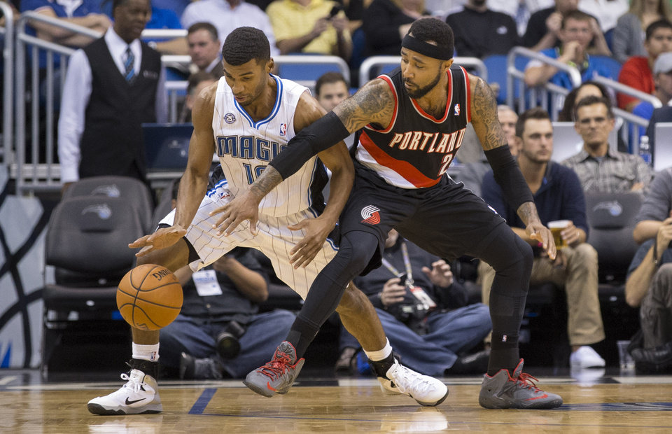 Photo - 3Orlando Magic's Ronnie Price (10) steals the ball from Portland Trailblazers Mio Williams (25) during the first half of an NBA basketball game in Orlando, Fla., Tuesday, March 25, 2014. (AP Photo/Willie J. Allen Jr.)