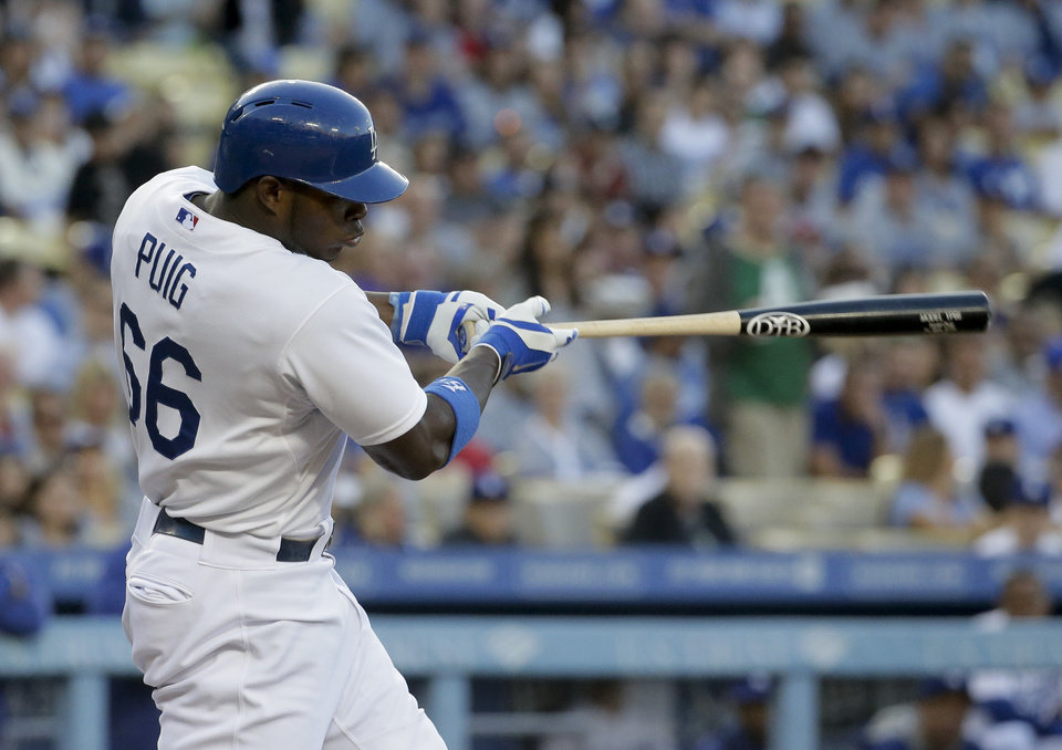 Photo - Los Angeles Dodgers right fielder Yasiel Puig hits a double against the Cleveland Indians during the first inning of a baseball game in Los Angeles, Tuesday, July 1, 2014. (AP Photo/Chris Carlson)