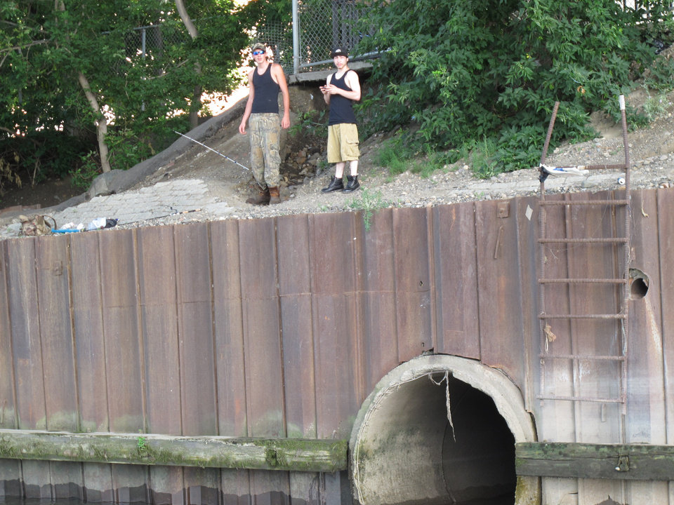 Two people prepare to fish beneath a bridge where a combined sewage overflow pipe empties into the Hudson River on Tuesday, July 23, 2013, in Troy, NY. Billions of gallons of untreated sewage flow into New York waterways annually, and environmental officials estimate $36 billion will be needed over the next 20 years for sewer system repairs and upgrades. (AP Photo/Mary Esch)