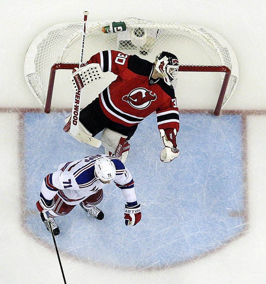 Photo -   New Jersey Devils goalie Martin Brodeur, top, reacts after being punched by New York Rangers' Mike Rupp, center, during the third period of Game 4 of an NHL hockey Stanley Cup Eastern Conference final playoff series, Monday, May 21, 2012, in Newark, N.J. The Devils won 4-1. (AP Photo/Julio Cortez)