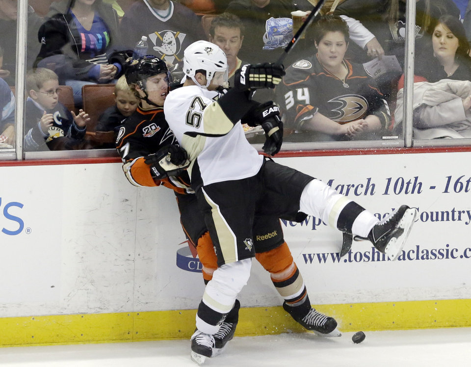 Photo - Anaheim Ducks defenseman Hampus Lindholm (47), of Sweden, and Pittsburgh Penguins center Marcel Goc (57), of Germany, tangle in the first period of an NHL hockey game in Anaheim, Calif., Friday, March 7, 2014.  (AP Photo/Reed Saxon)