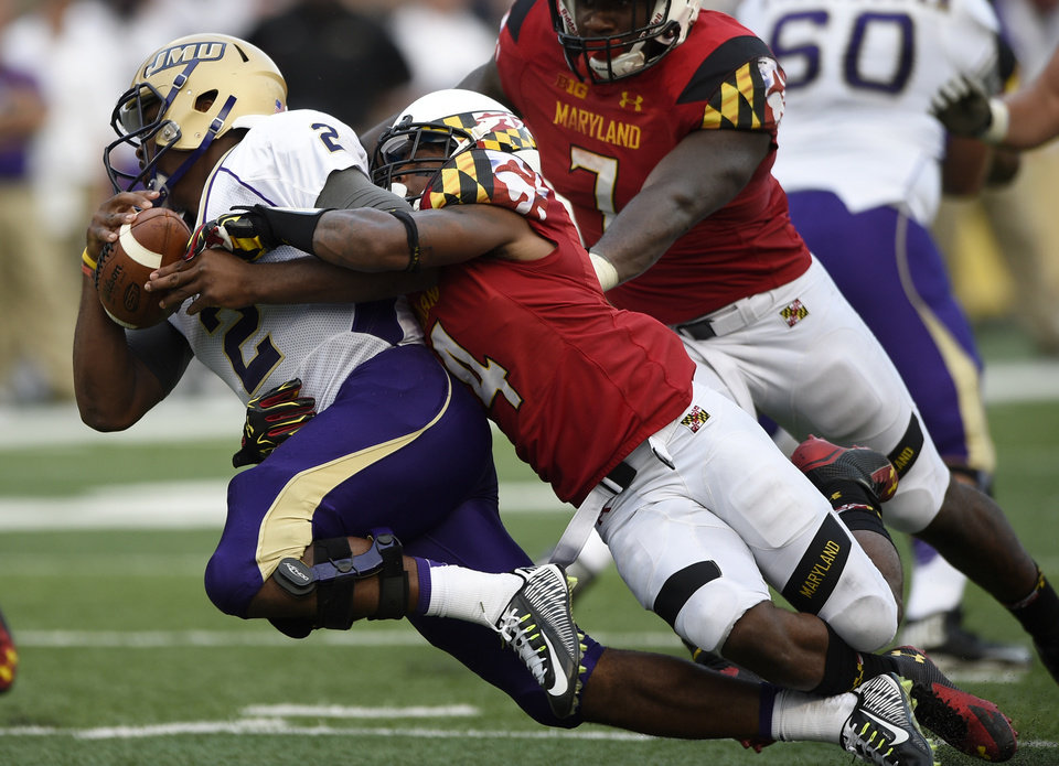 Photo - Maryland defensive back William Likely, right, sacks James Madison quarterback Vad Lee (2) during the second half of an NCAA football game, Saturday, Aug. 30, 2014, in College Park, Md. Maryland won 52-7. (AP Photo/Nick Wass)