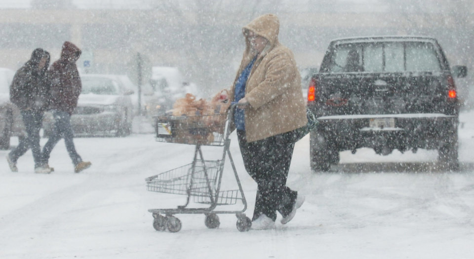 Photo - Shoppers buy groceries at the Kroger's in West State Plaza on W. State Blvd during a snow storm in Fort Wayne, Ind., Wednesday, Dec. 26, 2012. (AP Photo/The Journal Gazette, Cathie Rowand)
