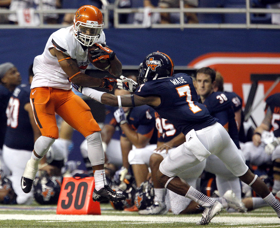 Photo - Oklahoma State's Josh Stewart (5) tries to get by UTSA's Triston Wade (7) during the first half of a college football game between the University of Texas at San Antonio Roadrunners (UTSA) and the Oklahoma State University Cowboys (OSU) at the Alamodome in San Antonio, Saturday, Sept. 7, 2013.  Photo by Sarah Phipps, The Oklahoman