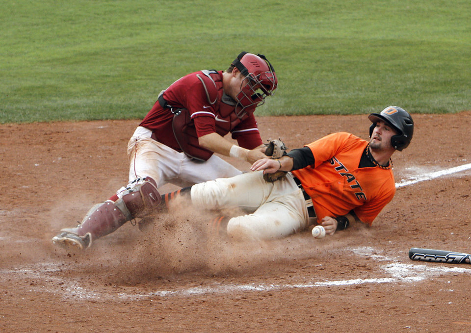 Photo - Oklahoma State's Robbie Rea scores the winning run as Oklahoma's Dylan Neal drops the ball during the Bedlam baseball game between the University of Oklahoma and Oklahoma State University at the Chickasaw Bricktown Ballpark in Oklahoma City, Sunday, May 6, 2012. Photo by Sarah Phipps, The Oklahoman