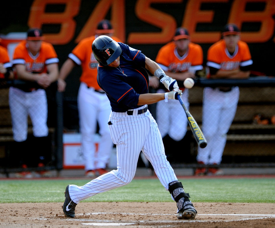 Photo - Fullerton designated hitter Greg Velazquez hits a double down the right field line allowing two teammates to score during the first inning of an NCAA college baseball regional tournament game against Oklahoma State, Sunday, June 1, 2014, in Stillwater, Okla. (AP Photo/Brody Schmidt)