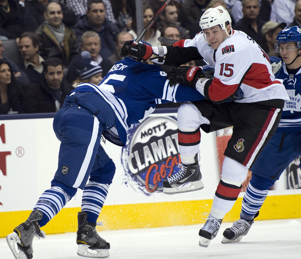 Toronto Maple Leafs defenseman Mark Fraser, left, knocks Ottawa Senators center Zach Smith (15) off the puck during first-period NHL hockey game action in Toronto, Wednesday, March 6, 2013. (AP Photo/The Canadian Press, Frank Gunn)