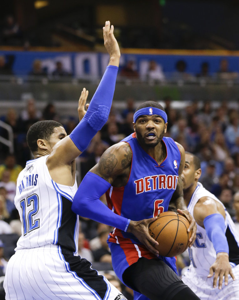 Photo - Detroit Pistons' Josh Smith (6) makes a move to the basket between Orlando Magic's Tobias Harris (12) and Arron Afflalo, right, during the first half of an NBA basketball game in Orlando, Fla., Friday, Dec. 27, 2013. (AP Photo/John Raoux)