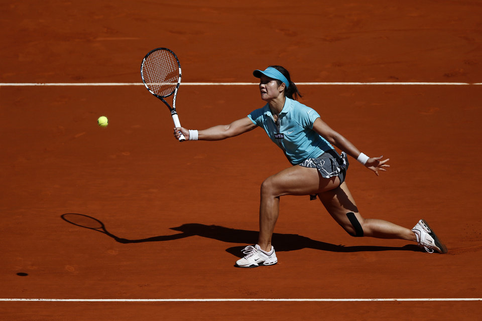 Photo - Na Li from China returns the ball during a Madrid Open tennis tournament match against Sloane Stephens from U.S. in Madrid, Spain, Thursday, May 8, 2014 . (AP Photo/Daniel Ochoa de Olza)