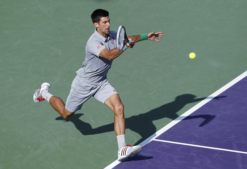 Photo - Novak Djokovic, of Serbia, returns the ball to Andy Murray, of Britain, at the Sony Open Tennis tournament in Key Biscayne, Fla., Wednesday, March 26, 2014. Djokovic defeatedMurray 7-5, 6-3. (AP Photo/Joel Auerbach)