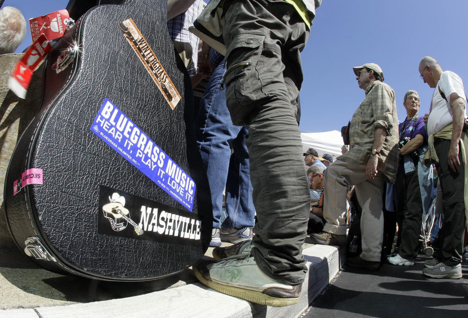 A musician holds his guitar case on Tuesday, Sept. 27, 2011, as he listens to a free outdoor concert in downtown Nashville, Tenn., during the week-long International Bluegrass Music Association celebration. (AP Photo/Mark Humphrey)