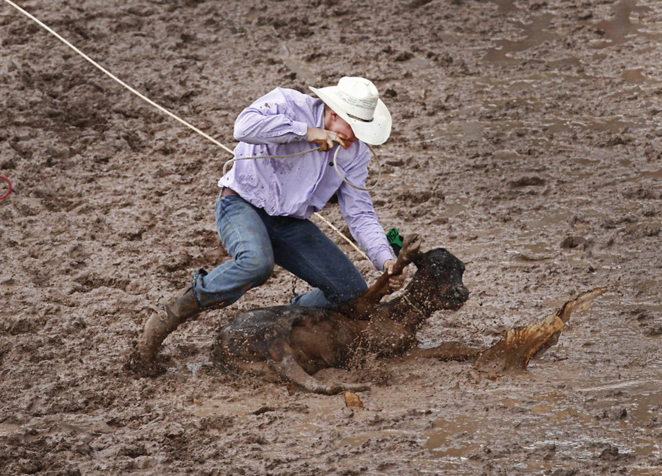Photo - Roy Lee, Benton, AR, compete in a muddy Calf Roping at the International Youth Finals Rodeo in Shawnee at the Heart of Oklahoma Exposition Center, Wednesday, July 9, 2014. Photo by David McDaniel, The Oklahoman